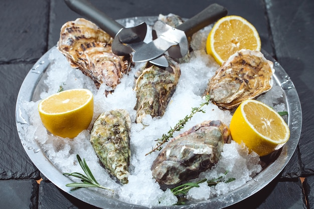 Ostriche sul piatto di pietra con ghiaccio e limone.