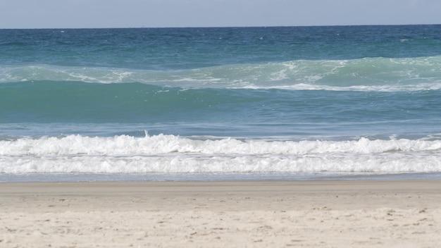 Grandi onde dell'oceano pacifico che spruzzano, costa della california usa. struttura della superficie dell'acqua e schiuma di mare. vista sul mare vicino alla spiaggia sabbiosa, acqua blu. inquadratura dal basso della marea turchese. giornata di sole estivo ventoso tropicale.