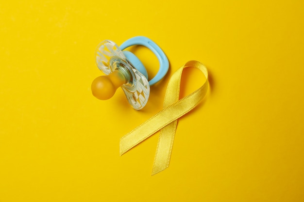 Ciuccio e nastro di consapevolezza del cancro del bambino su sfondo giallo
