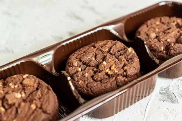 Confezione di biscotti al cioccolato americano con noci su fondo di legno bianco. pasticceria fresca.