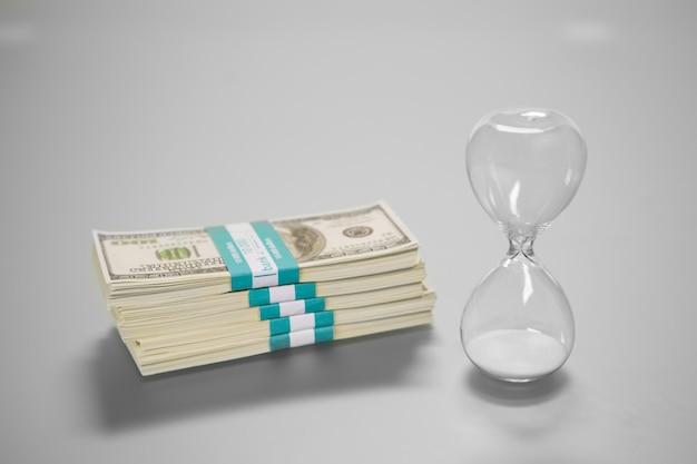 Confezione di contanti e clessidra. due cose che contano. scegliere saggiamente. quello che finisce per primo.