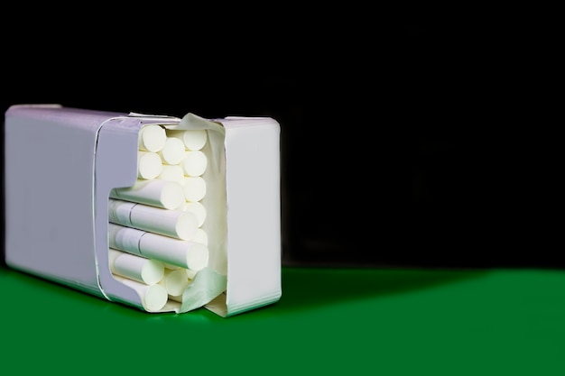 Un pacchetto di sigarette su uno sfondo scuro accanto a uno sfondo verde