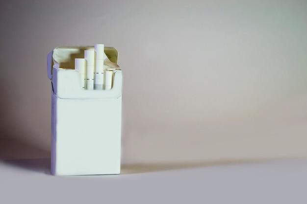 Un pacchetto di sigarette su uno sfondo grigio chiaro solitudine