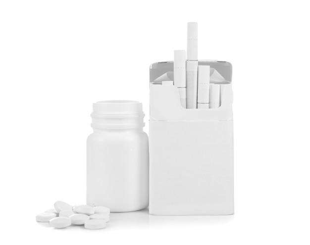 Pacchetto di sigarette e pillole isolato su bianco