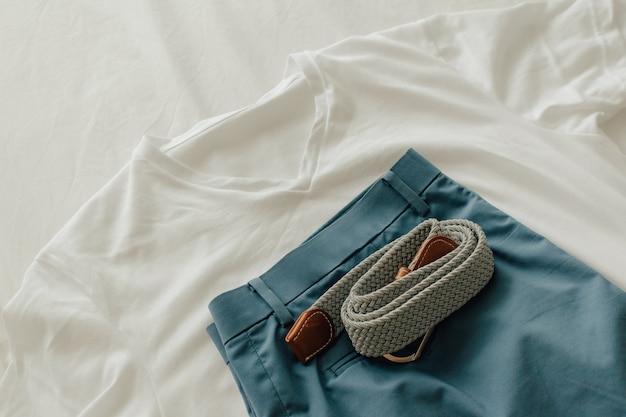 Confezione di vestiti sul letto bianco con una maglietta bianca corta blu e cintura da vestire.