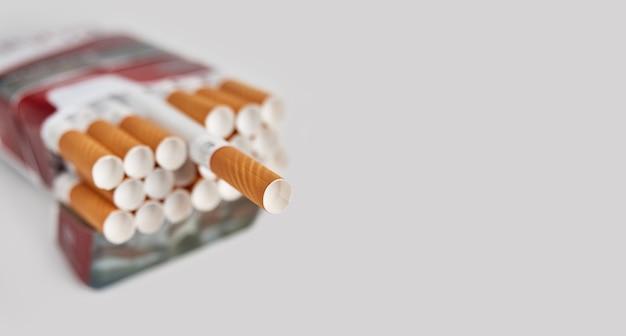 Pacchetto pieno di sigarette con filtro su una superficie grigia