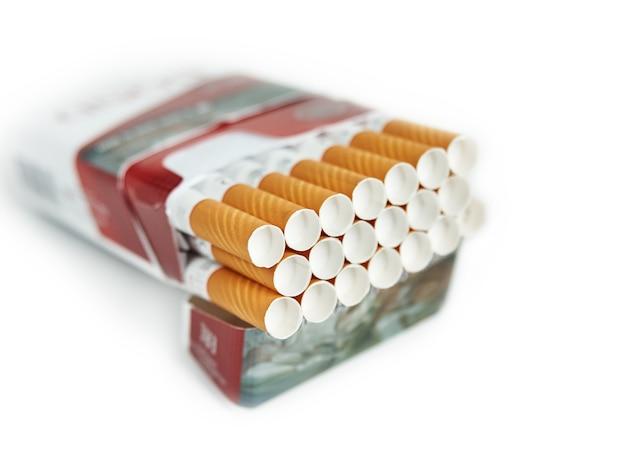 Pacchetto pieno di sigarette filtrate sulla superficie isolata bianca