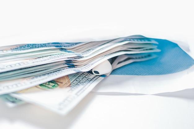 Confezione di banconote da cento dollari insieme a un bug si trovano in una busta. il concetto di concussione e corruzione. tecnica mista