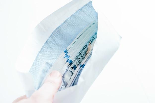 Pacchetto di banconote da cento dollari si trova in una busta. il concetto di concussione e corruzione. tecnica mista