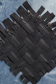 Confeziona un sacco di strisce di cerniere in ottone in metallo nero con motivo a cursori per cucito a mano, sartoria, pelletteria, pelletteria sullo sfondo di legno blu