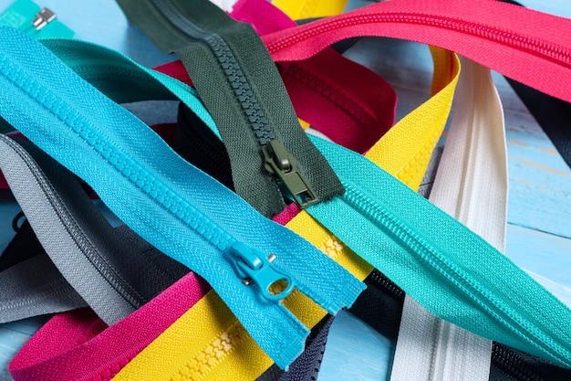 Confeziona un sacco di strisce di cerniere in plastica colorate con motivo a cursori per cucire a mano sartoria su sfondo blu denim close up fuoco selettivo