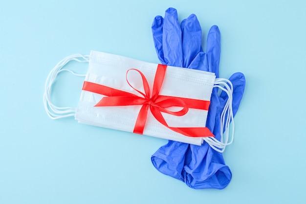 Confezione di maschere mediche come regalo con nastro rosso e guanti protettivi su sfondo azzurro.