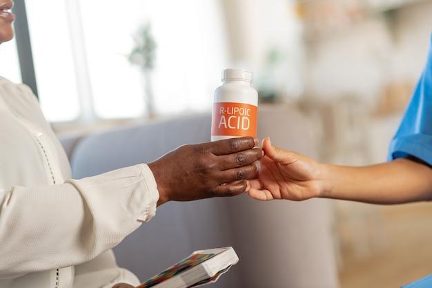 Confezione con vitamine. donna che indossa una camicetta bianca che prende il pacco con le vitamine dall'infermiera al mattino