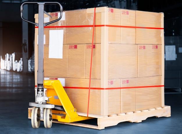 Scatole per pacchi su pallet con transpallet manuale nel magazzino spedizione del carico