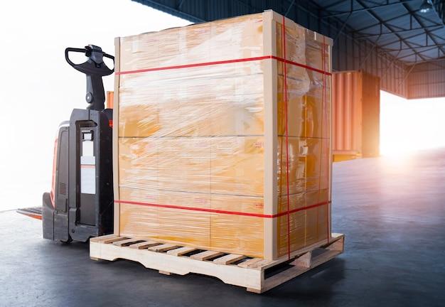 Scatole per pacchi pellicola di plastica avvolta su pallet con carrello elevatore elettrico pallet jack cargo box spedizione
