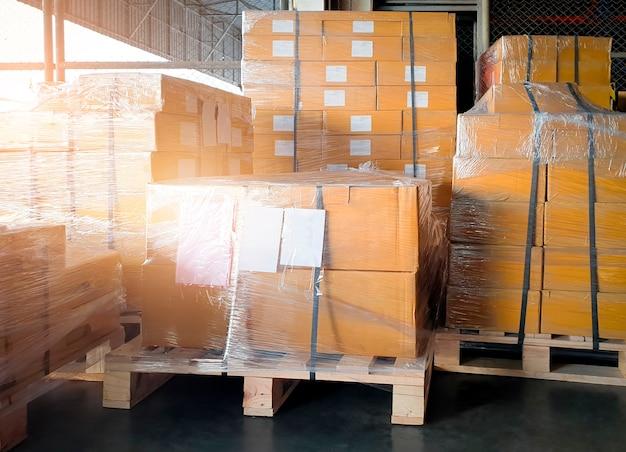 Scatole per pacchi pellicola di plastica avvolta su pallet presso il magazzino di stoccaggio scatole per la spedizione del carico