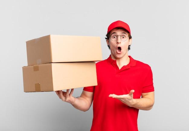 Il pacco consegna un ragazzo che sembra sorpreso e scioccato, con la mascella caduta in possesso di un oggetto con una mano aperta sul lato