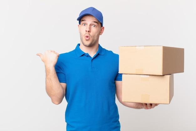 Il pacco consegna l'uomo che sembra stupito per l'incredulità, indicando l'oggetto sul lato e dicendo wow, incredibile