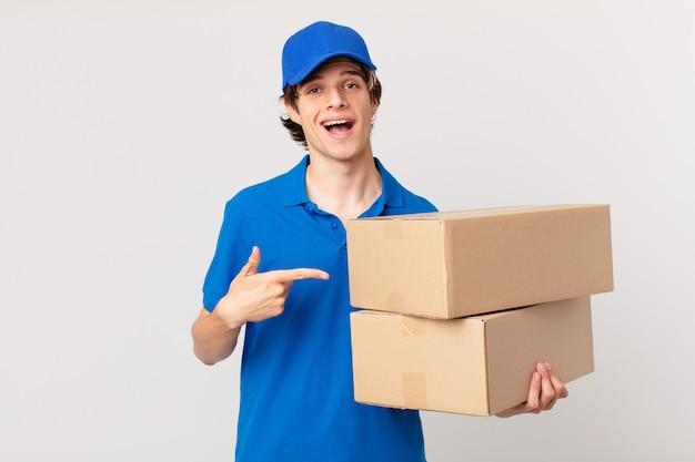 Il pacco consegna l'uomo che sembra eccitato e sorpreso che indica il lato