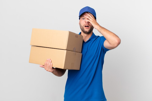 Il pacco consegna l'uomo che sembra scioccato, spaventato o terrorizzato, coprendo il viso con la mano
