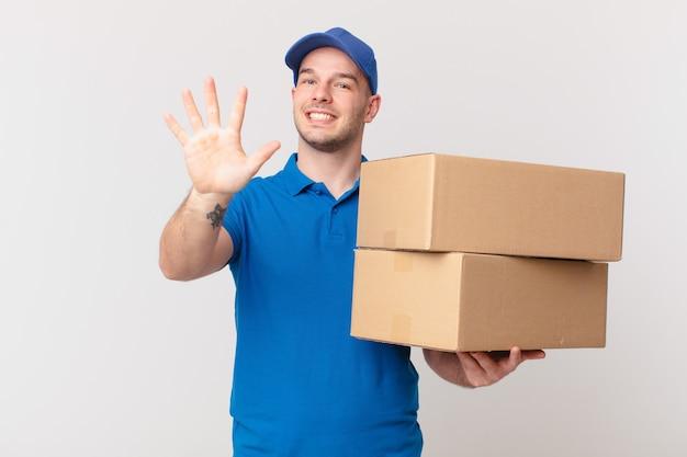 Il pacchetto consegna l'uomo sorridente e dall'aspetto amichevole, mostrando il numero cinque o il quinto con la mano in avanti, conto alla rovescia