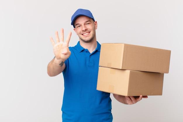 Il pacchetto consegna l'uomo sorridente e dall'aspetto amichevole, mostrando il numero quattro o il quarto con la mano in avanti, conto alla rovescia