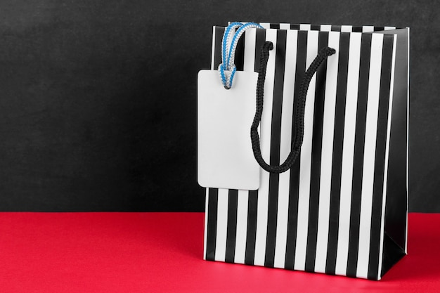 Pacchetto per acquisti in una striscia con un cartellino del prezzo su un tavolo rosso su sfondo nero con un posto per un'iscrizione. concetto di venerdì nero. shopping