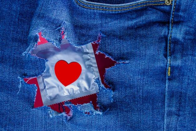 Preservativo confezionato con un cuore rosso in pantaloni di jeans strappati. amore e romanticismo. sesso sicuro. offerta sessuale. carta di san valentino.