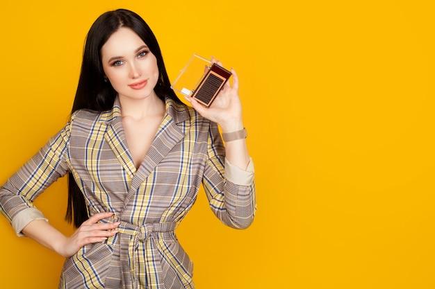 Imballaggio di ciglia artificiali nelle mani di un maestro di estensione delle ciglia, su una parete gialla. il concetto di estensioni delle ciglia, pubblicità per materiale per saloni di bellezza.