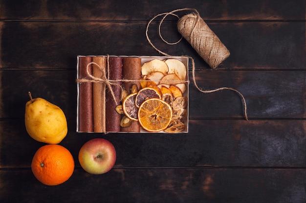 Scatole di confezionamento con snack dolci di frutta - pastiglie, frutta secca e frutta fresca - pera, mela, arancia.