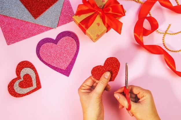 Confezione regalo di san valentino o compleanno. regali di san valentino con un cuore di carta rosso su una superficie rosa. vista dall'alto. fai da te. la donna ha tagliato il cuore rosso dalla carta. passo dopo passo