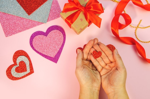 Confezione regalo di san valentino o compleanno. regali di san valentino con un cuore di carta rosso su una superficie rosa. vista dall'alto. le mani femminili tengono il cuore di carta rosso.