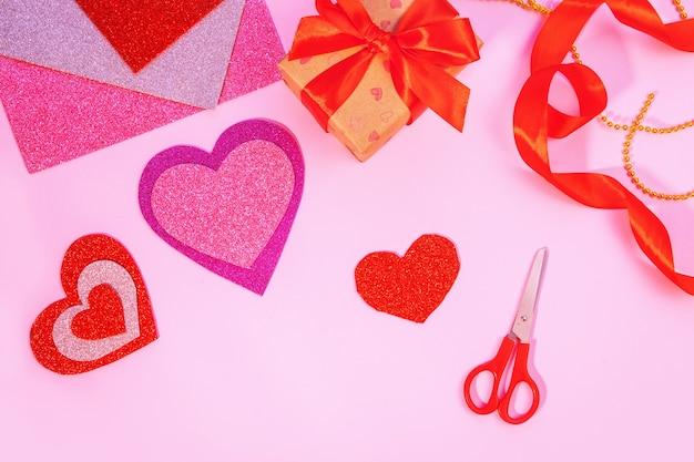 Confezione regalo di san valentino o compleanno. regali di san valentino con un cuore di carta rosso su una superficie rosa. vista dall'alto. strumenti per cuori di carta artigianale.