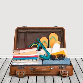 Valigia vintage piena di articoli per le vacanze