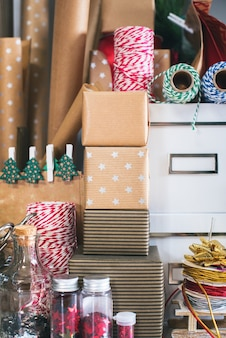Scatole da imballaggio, regali in carta kraft beige vintage. bacca dell'agrifoglio della corona sul fondo grigio della parete. concetto di preparazione al capodanno e alle vacanze di natale
