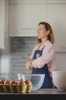Imballaggio di uova e ciotole per fare l'impasto sullo sfondo della cucina e della donna che cucina a casa