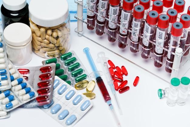 Confezioni di pillole e capsule di medicinali e provette per analisi del sangue