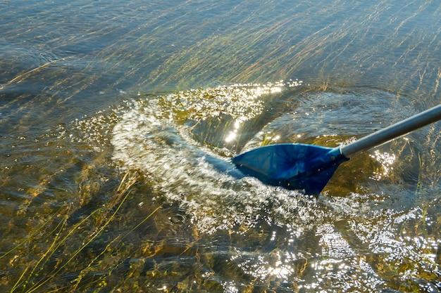 La pagaia della barca tocca l'acqua e provoca schizzi e increspature nell'acqua. pagaia blu e il suo riflesso nel fiume durante la navigazione su una barca, catamarano