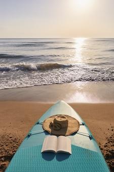Paddle surf nella sabbia sulla spiaggia all'alba