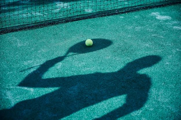Campo da paddle tennis con una palla e l'ombra di un giocatore