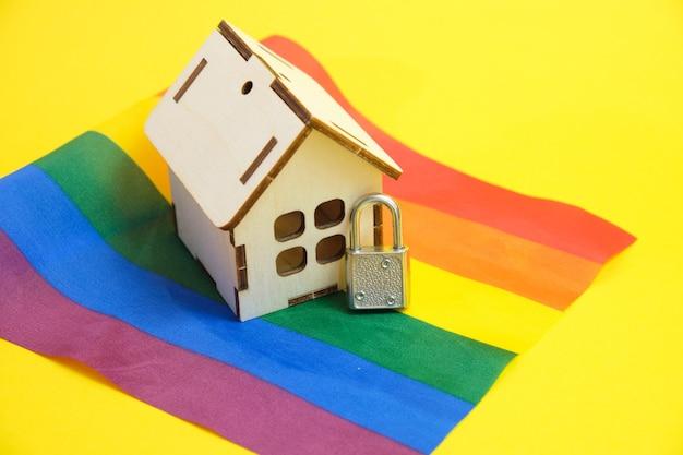 Lucchetto e piccola casa sulla bandiera della comunità lgbt, sicurezza e privacy del concetto di coppie dello stesso sesso
