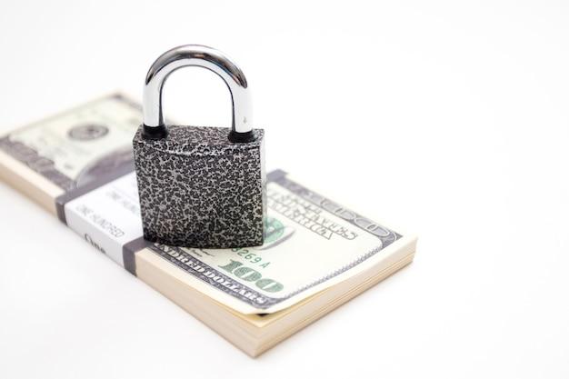 Pacchetto di banconote in dollari usa e lucchetto.