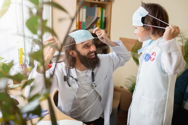 Medico pediatra che esamina un bambino in uno studio medico confortevole