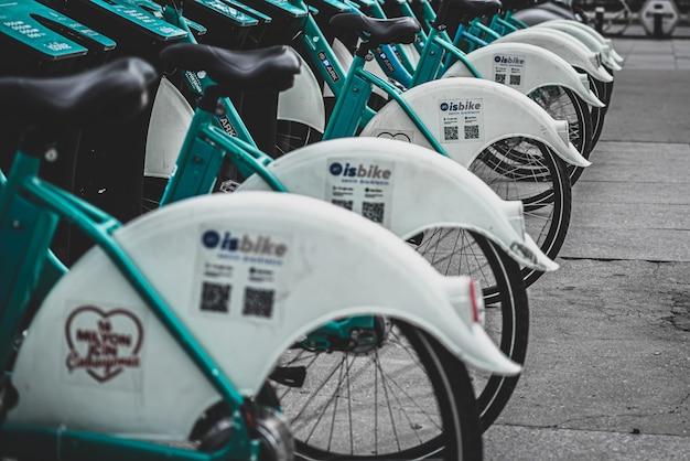 Bici verdi a pagamento in piedi una accanto all'altra fianco a fianco