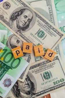 Iscrizione a pagamento su cubi di legno sulla trama di dollari americani e banconote in euro