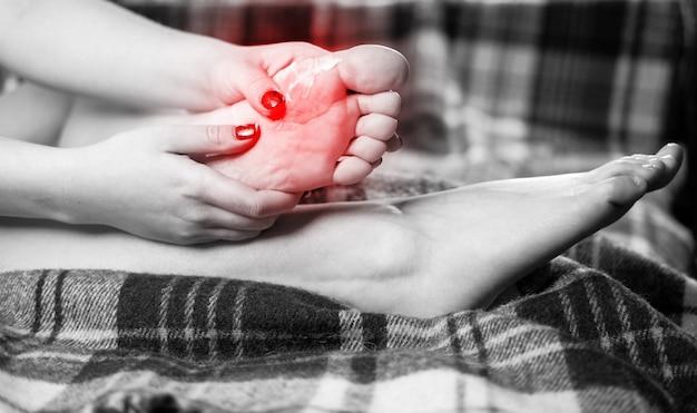 Dolore al piede, la ragazza tiene le mani ai piedi, massaggio ai piedi