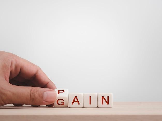 Concetto di dolore o guadagno. chiuda in su alfabeti di tornitura a mano su blocchi di cubo di legno per cambiare le parole sulla scrivania in legno e sullo sfondo bianco con spazio di copia.