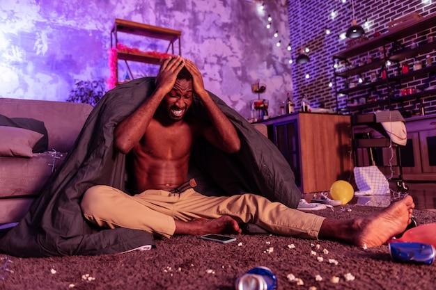 Dolore e sbornia. uomo dalla pelle scura con doloroso mal di testa la mattina dopo la festa mentre era seduto in una stanza decorata e sporca