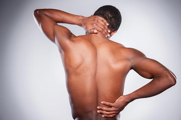 Dolore alle articolazioni. vista posteriore di un giovane africano senza camicia che si tocca il collo e l'anca mentre si trova in piedi su uno sfondo grigio
