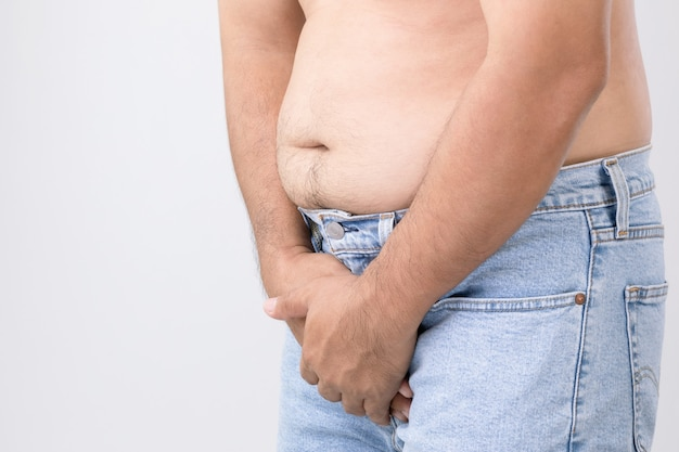 Concetto di dolore al pene: l'uomo usa le mani per premere sul suo pene sul muro grigio. usato per il cancro alla prostata